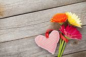 Colorful gerbera flowers and Valentine's day heart toy. On wooden background with copy space