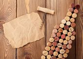 Wine bottle shaped corks, corkscrew and piece of paper for copy space over rustic wooden table background. Top view