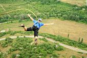 picture of sky diving  - Jump off a cliff with a rope on the background of mountains and sky - JPG