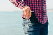 pic of denim jeans  - Woman takes out mobile phone of her pocket of jeans on beach near the sea to make self - JPG