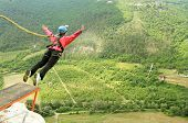 stock photo of sky diving  - Jump off a cliff with a rope on the background of mountains and sky - JPG
