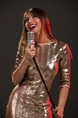 stock photo of singing  - A young woman in sequin dress singing in front of a microphone with a wide open mouth and expression of happiness on her face - JPG