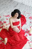 Portrait of a beautiful pregnant woman in red chiffon shawl