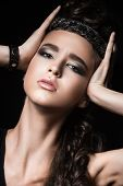 Beautiful dark-haired girl with bright makeup and jewelry made of leather. Beauty face. Punk style.