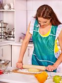 Young happy woman cooking at kitchen. Girl rolls  dough with  rolling pin