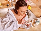 Woman relaxing at home luxury bath. Girl put the cream on face
