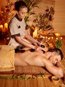 Man getting stone therapy massage in bamboo spa. Burning candles