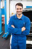 Mechanic smiling at the camera at the repair garage