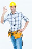 Portrait of happy handyman gesturing OK sign over white background
