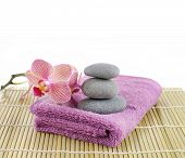 Branch orchid and stones on pink towel on mat