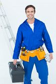 Portrait of confident repairman carrying tool box over white background