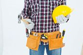 Cropped image of handyman wearing tool belt while holding hard hat and hammer on white background