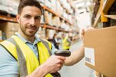 Warehouse worker scanning box while smiling at camera in a large warehouse