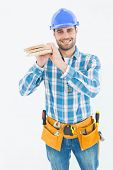 Portrait of happy carpenter carrying wooden planks against white background