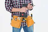 Cropped image of male handyman holding drill machine over white background
