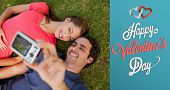 Man taking a photo with his friend while lying side by side against cute valentines message