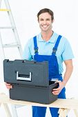 Portrait of happy carpenter opening tool box at table against white background