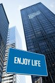 The word enjoy life and blue billboard against low angle view of skyscrapers