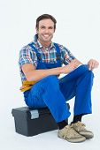 Portrait of happy plumber writing notes while sitting on tool box over white background