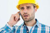 Male carpenter using cellphone against white backgorund