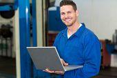 Smiling mechanic using his laptop at the repair garage