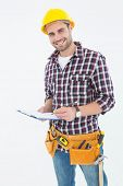 Portrait of confident male repairman writing on clipboard over white background