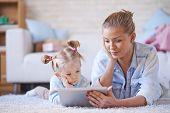 Young mother and daughter with digital tablet lying on the floor and resting online