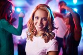 Cheerful girl looking at camera on background of dancing friends at party
