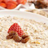 closeup of a bowl with porridge with sultana raisins and strawberry