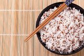 Bowl Of White Rice And Quinoa With Chopsticks On Bamboo Mat.