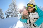 Man giving girlfriend piggyback ride in the snowy mountain