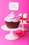 Delicious cupcake with inscription on pink background