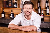 stock photo of bartender  - Handsome young male bartender in white shirt leaning at the bar counter and smiling - JPG