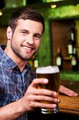 image of toothless smile  - Handsome young man toasting with beer and looking at camera with smile while sitting at the bar counter - JPG