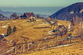 picture of household farm  - Peaceful Romanian rural scene with traditional farm and grassland uphill in Moeciu Brasov county Trasylvania region Romania - JPG