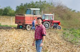 picture of tractor-trailer  - Smiling young farmer standing on field with tractor and trailer in background - JPG
