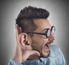 stock photo of nerds  - Nerd man listens with curiosity a gossip - JPG