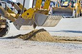 stock photo of bulldozers  - Close up of bulldozer bucket collecting sand on construction site in urban area - JPG