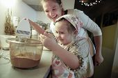 stock photo of cake-mixer  - Mother smiling and tutoring her daughter in the kitchen as she is preparing dough for homemade Christmas cake - JPG