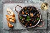 picture of slating  - Mussels in copper cooking dish and French Baguette with herbs on stone slate background - JPG