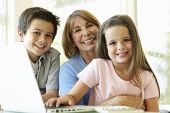 picture of grandmother  - Hispanic Grandmother Using Laptop With Grandchildren - JPG