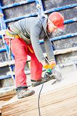picture of millwright  - builder carpenter worker with disk saw cutting plywood for falsework construction before concreting at building site - JPG