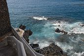 foto of stairway  - View of surf in rocks and stones at coast between Arena and Chico beaches from stairway behind buildings on Maritima Street in Puerto de Santiago Tenerife Canary Islands Spain - JPG