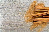 image of cinnamon sticks  - Sticks and powder of cinnamon on a wooden table - JPG