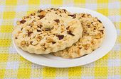 foto of shortbread  - Two shortbreads rings with peanuts in white glass plate on yellow tablecloth - JPG