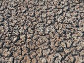 stock photo of drought  - dry sandy cracked ground from dried lake bed resulting from drought - JPG