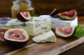 picture of jar jelly  - Fresh figs on wooden cutting chopping board with jar of fig jelly preserve and gourmet cheese on dark wood rustic table background close up - JPG