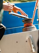 pic of yachts  - Male hand on winch capstan with rope on sailing boat - JPG