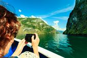 picture of fjord  - Tourism vacation and travel. Woman tourist taking photo with camera view from deck of ship on fjord Sognefjord in Norway Scandinavia. ** Note: Visible grain at 100%, best at smaller sizes - JPG