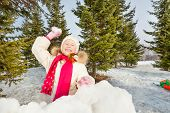 image of snowball-fight  - Laughing girl ready to throw snowball while standing behind the snow wall with fir forest on the background during beautiful winter day - JPG